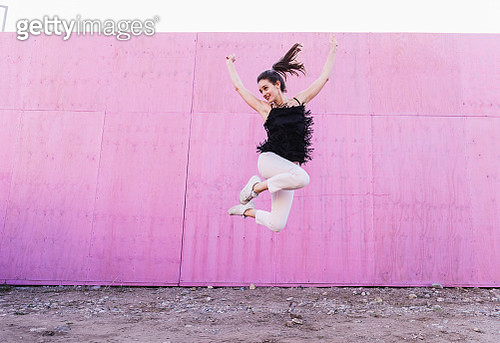Exuberant young woman jumping in front of pink wall - gettyimageskorea