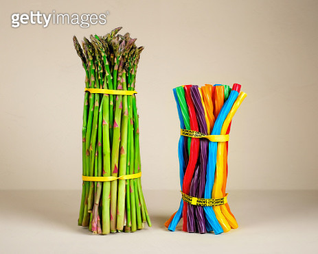 A bunch of asparagus bound with rubber bands next to a bunch of brightly colored licorice twists bound with a rubber band on a neutral background representing food choices. - gettyimageskorea
