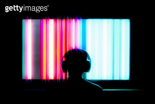 Silhouetted person with headphones watching large tv screen - gettyimageskorea