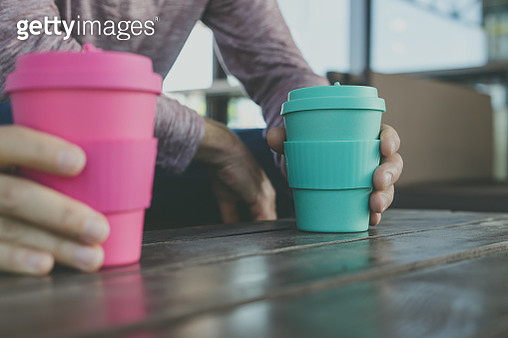 Couple holding reusable takeaway coffee cups on wooden pallet upcycled table, outdoors, selective focus - gettyimageskorea