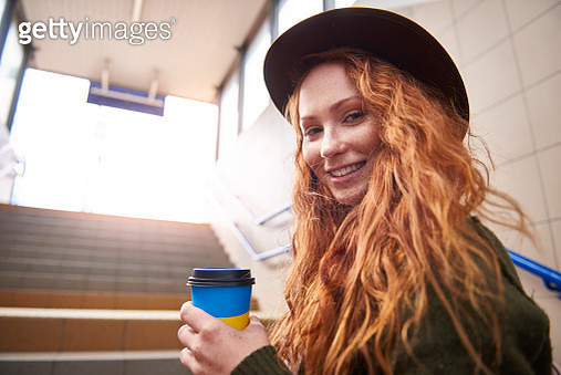 Portrait of smiling redheaded woman with coffee to go - gettyimageskorea
