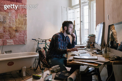 Young creative man working in his home office. He is looking at computer screen - gettyimageskorea