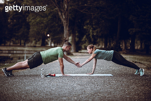 Couple Making Tag Fitness Push-Ups Together On Exercise Mat In Public Park - gettyimageskorea