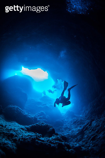 Low Angle View Of Scuba Divers Swimming In Cave - gettyimageskorea