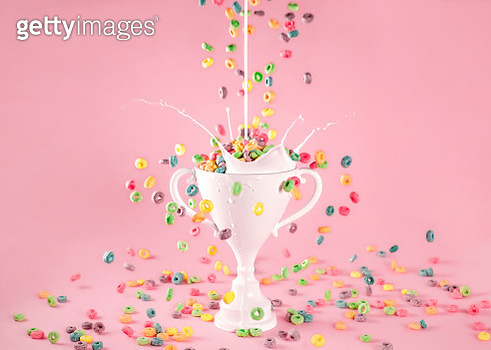 white loving cup trophy filled with colorful fruit cereal featuring a milk splash on a pink background. - gettyimageskorea