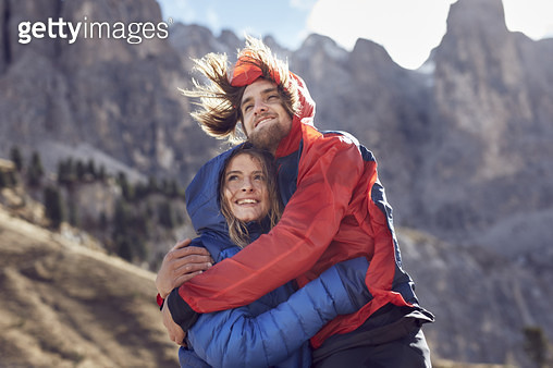 Happy young couple hugging in windy mountains - gettyimageskorea