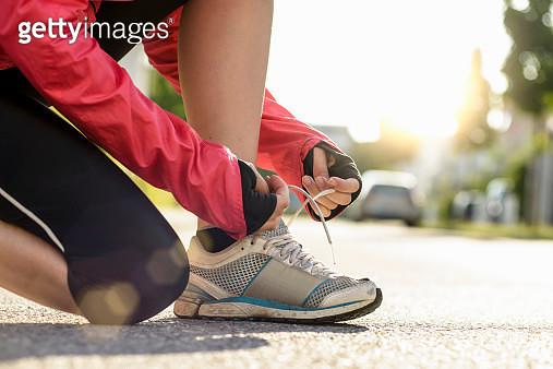 female runner tying shoe lace in a urban area - gettyimageskorea