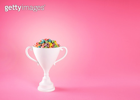 white loving cup trophy filled with colorful fruit cereal on a pink background. - gettyimageskorea