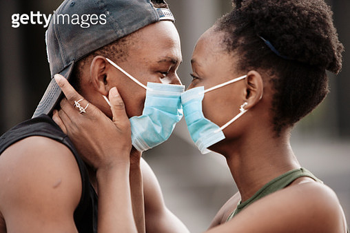 Beautiful young couple wearing surgical face masks at close range - gettyimageskorea