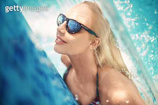 Beautiful woman with sunglasses enjoying jet of water in the pool. - gettyimageskorea