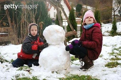 Cute Siblings Making Snowman During Winter - gettyimageskorea