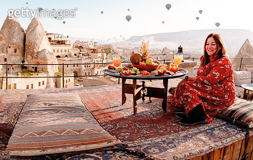 Woman dressed in red on a rooftop in Cappadocia at sunrise, Turkey - gettyimageskorea