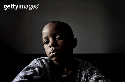 Portrait Of Boy Sitting At Home Against Wall - gettyimageskorea
