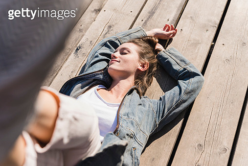 Relaxed young woman lying on wooden boards in sunshine - gettyimageskorea