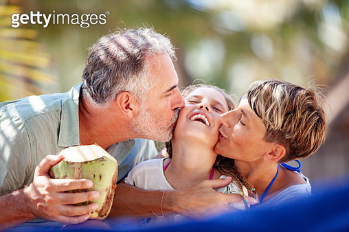 Mother and Father Kissing Daughter on Tropical Vacations - gettyimageskorea