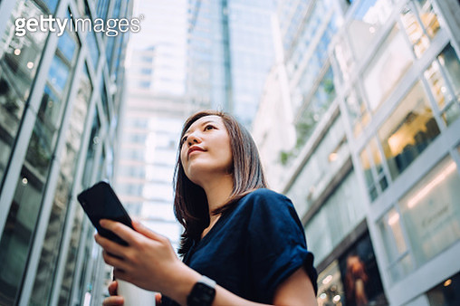 Low angle portrait of confidence and successful young Asian businesswoman with coffee to go, using smartphone while standing against highrise corporate buildings in financial district in the city - gettyimageskorea