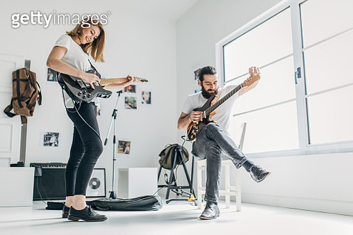Two people, young heterosexual couple, man and woman playing guitars, in home studio. - gettyimageskorea