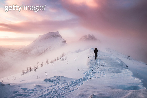 Man Walking On Snowcapped Mountain Against Sky During Sunset - gettyimageskorea