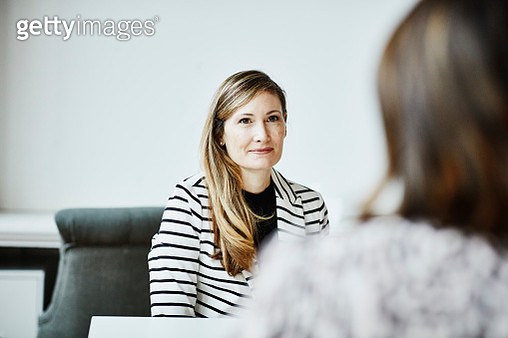 Female financial advisor in discussion with client during meeting in office - gettyimageskorea