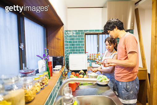 A couple is preparing vegetarian food in her zero waste kitchen. She is using a stainless straw to drink her beverage. She is decorating her kitchen counter with flowers in a glass bottle that she is up cycling and not throwing away. She has a zero waste  - gettyimageskorea