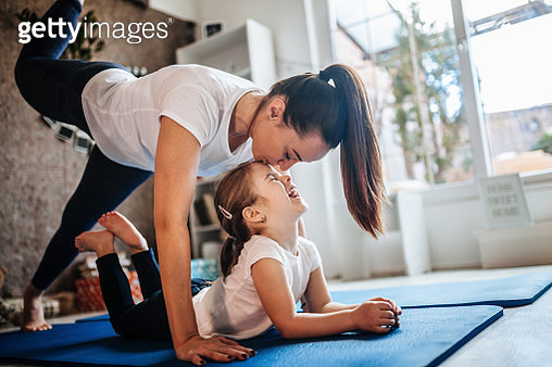 Mother and daughter working out together doing exercise at home - gettyimageskorea