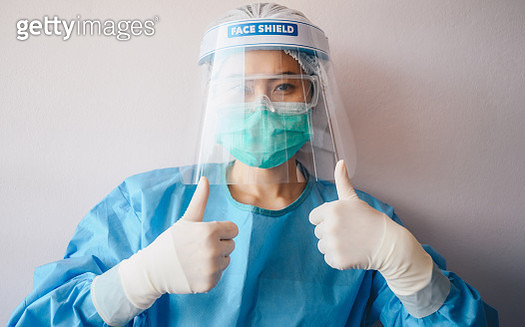 Nurse wearing medical scrubs, mask and face shield for protection virus disease while working longtime in hospital during covid-19 pandemic and her showing thumbs up. - gettyimageskorea