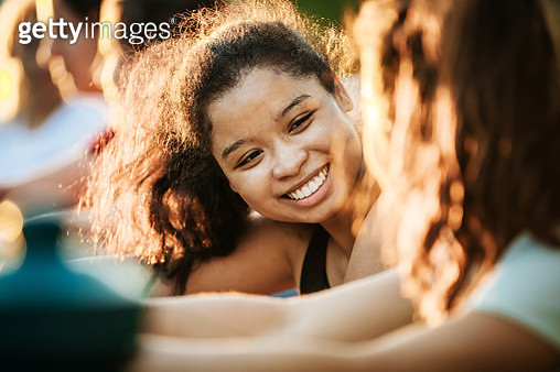 A young woman smiling while out with her fitness group, warming up before a run. - gettyimageskorea