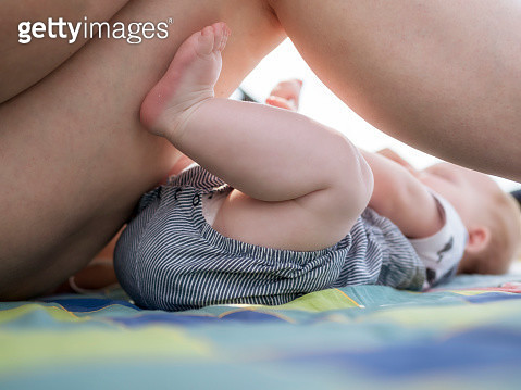 Baby girl lying on blanket close to mother - gettyimageskorea