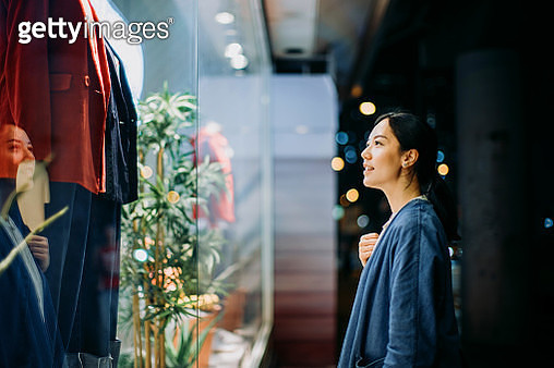 Young Asian woman looking at shop window while walking in the city at night - gettyimageskorea
