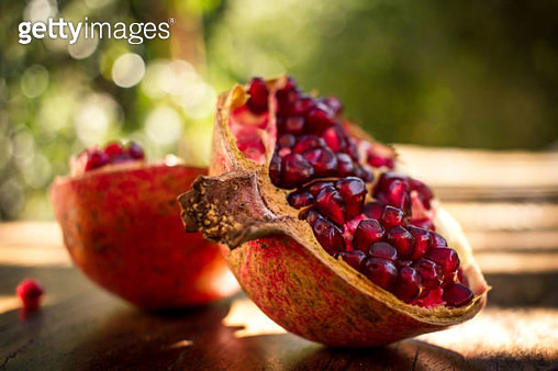 Ruby Red Pomegranate split open on a wooden table with green foliage as a blurred background. - gettyimageskorea