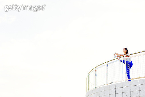 Young woman exercising outdoors, stretching leg on railing, South Point Park, Miami Beach, Florida, USA - gettyimageskorea