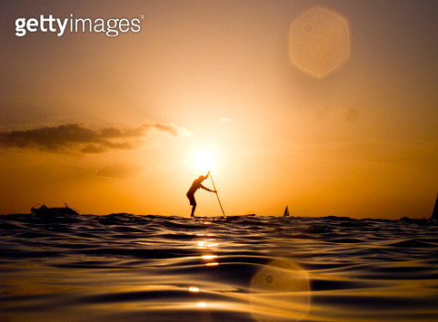 A paddler at sunset over the ocean in Waikiki, Hawaii. - gettyimageskorea