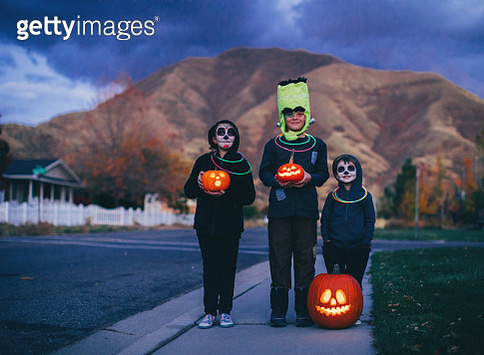 Three young children, two boys and one girl, are dressed as skeletons and Frankenstein for Halloween. They are ready to trick or treat for candy while holding illuminated Jack O' Lanterns in a local residential neighborhood. Image taken in Utah, USA. - gettyimageskorea