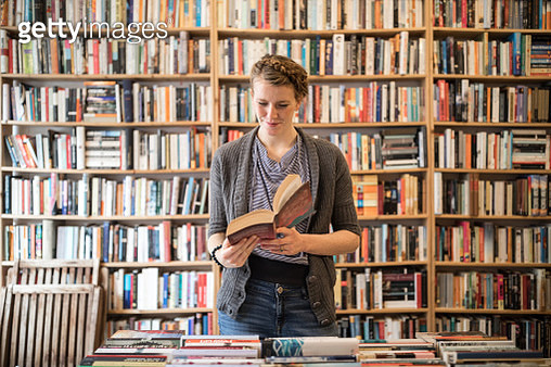 Smiling beautiful young female customer reading book standing against bookshelf at bookstore - gettyimageskorea
