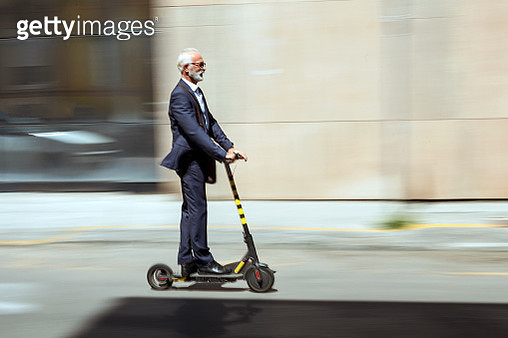 Businessman riding a electric scooter in the city - gettyimageskorea