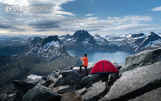 Man take a photo on the rock of Segla mountain, Senja, Norway - gettyimageskorea