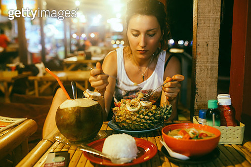 Pad Thai with shrimps served in a pineapple and a coconut water juice - gettyimageskorea