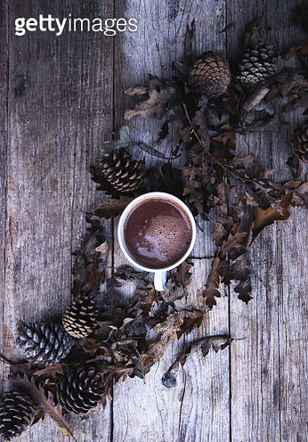Directly Above Shot Of Hot Chocolate Cup With Pine Cones And Oak Leaves On Table - gettyimageskorea
