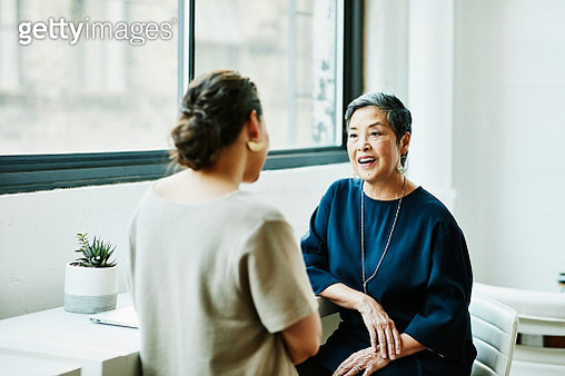 Smiling senior businesswoman in discussion with client in office conference room - gettyimageskorea