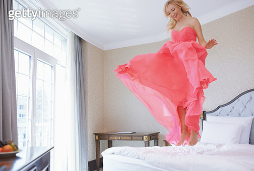 Happy bride in the pink wedding dress flying over the bed - gettyimageskorea