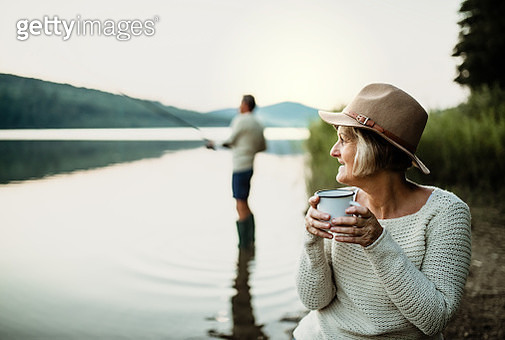 A senior couple fishing on a lake at sunset. - gettyimageskorea