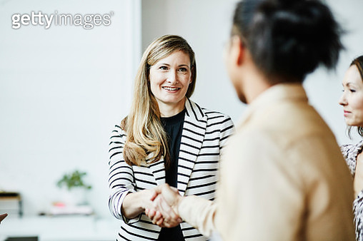 Smiling businesswoman shaking hands with client before meeting - gettyimageskorea