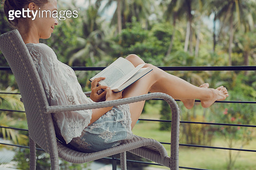 Young woman reading a book while relaxing on tropical island - gettyimageskorea