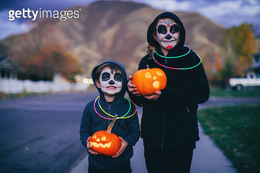 Two young children, a boy and a girl, are dressed as a calaveras skeletons for Halloween. They are ready to trick or treat for candy while holding illuminated Jack O' Lanterns in a local residential neighborhood. Image taken in Utah, USA. - gettyimageskorea