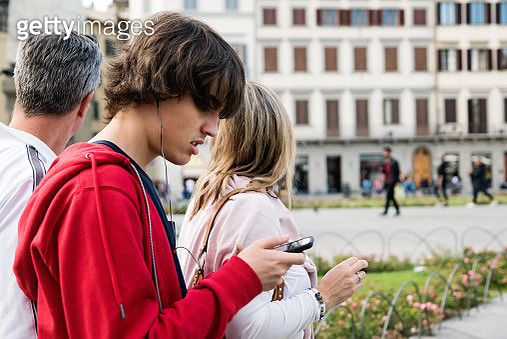 Mature couple and their teenage son discovering the city of Florence Italy. Here they are trying to find their way looking on the mobile phone map. They are all wearing casual clothes for early fall on a warm day. Horizontal waist up outdoors shot with co - gettyimageskorea