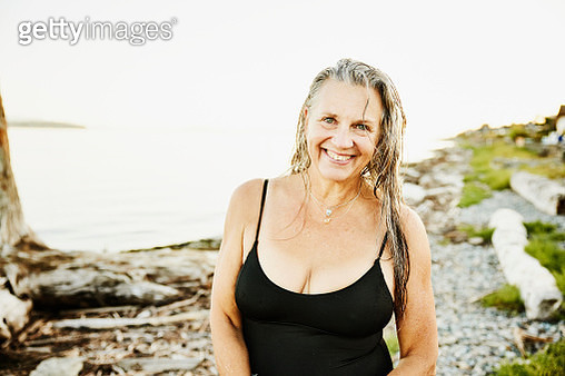 Portrait of smiling senior woman standing on beach after swim on summer evening - gettyimageskorea