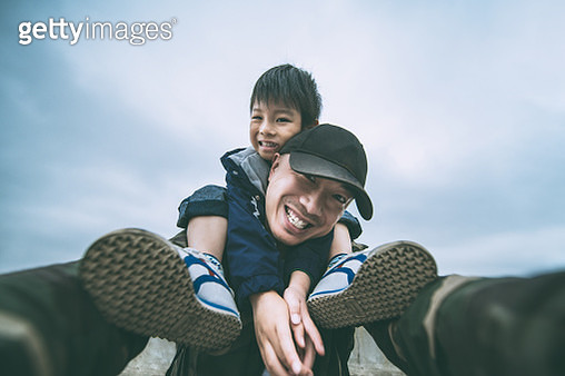Low angle view selfie portrait of the son sitting on his father's shoulder, Shanghai, China - gettyimageskorea
