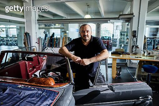 Portrait of man at vintage car in an automobile upholstery workshop - gettyimageskorea