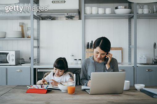 Young Asian mother working from home on a laptop and talking on the phone while little daughter is studying from home. She is attending online school classes with a digital tablet and doing homework at home - gettyimageskorea