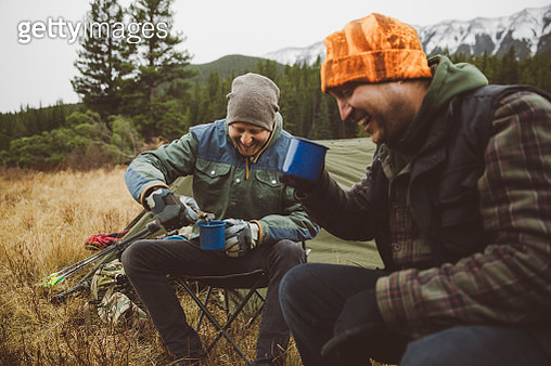 Smiling male hunter friends drinking coffee outside tent at campsite in remote field - gettyimageskorea